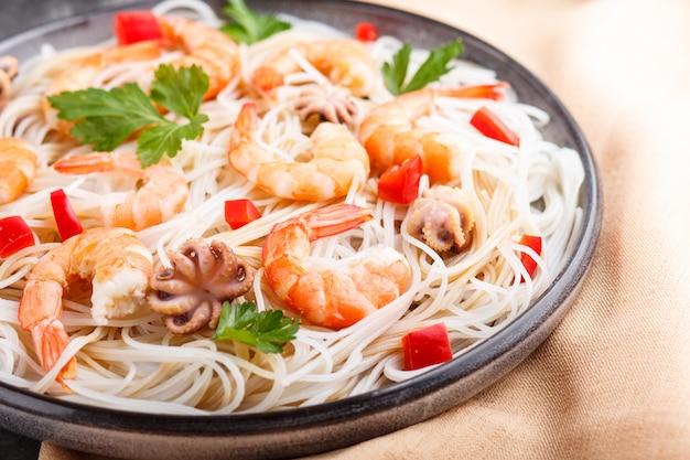 Macarrão de arroz com camarão ou camarão e polvos pequenos na placa de cerâmica cinza sobre um fundo preto de concreto Foto Premium