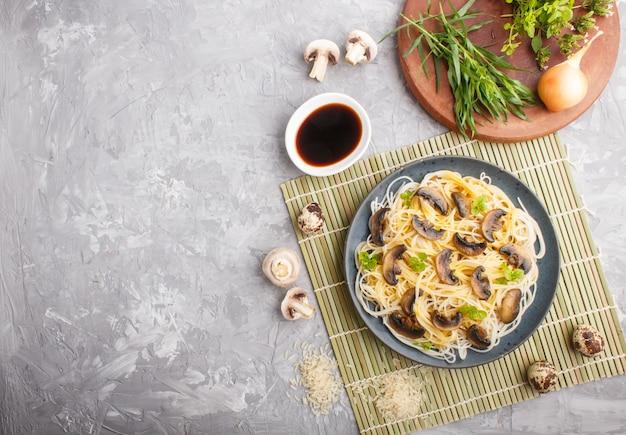 Macarrão de arroz com cogumelos champignon em um concreto cinza. vista do topo. Foto Premium