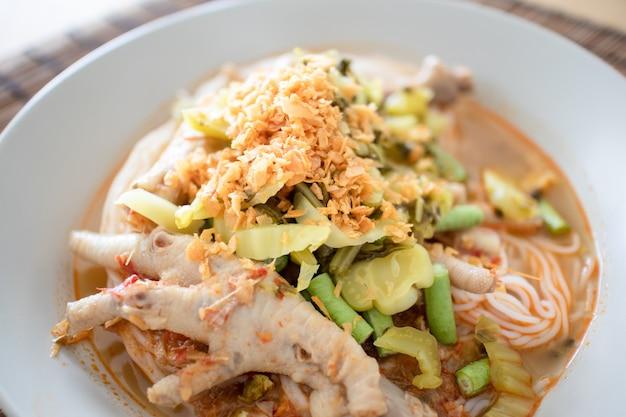 Macarrão de arroz em molho de caril de peixe com pés de galinha. Foto Premium