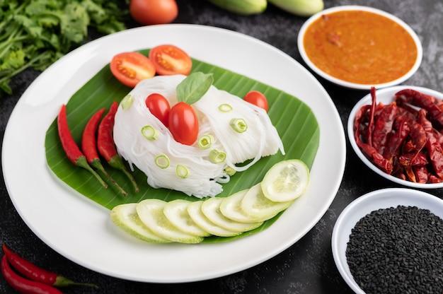 Macarrão de arroz em uma folha de bananeira com legumes e pratos maravilhosamente dispostos. comida tailandesa. Foto gratuita