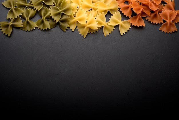 Macarrão de cru italiano fresco gravata sobre fundo preto, com espaço de cópia para escrever texto Foto gratuita