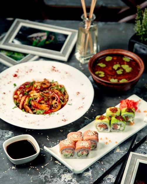 Macarrão de frango em cima da mesa com rolos de sushi Foto gratuita