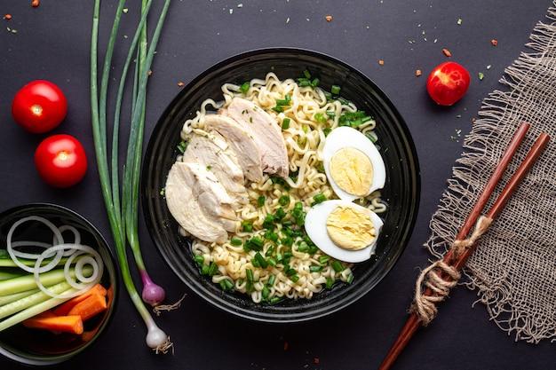Macarrão de ramen asiático com frango, legumes e ovo em uma tigela preta sobre fundo preto. vista do topo. Foto Premium