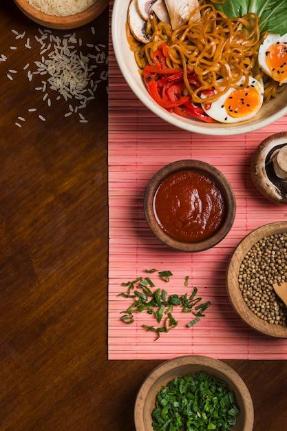 Macarrão de ramen com ovo; salada; cebolinha; sementes de coentro; grãos de arroz e molho na mesa de madeira Foto gratuita
