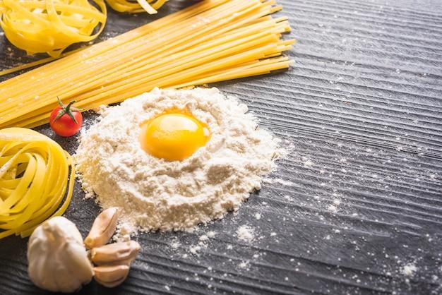 Macarrão de tagliatelle e espaguete com ingredientes no cenário de prancha de madeira Foto gratuita