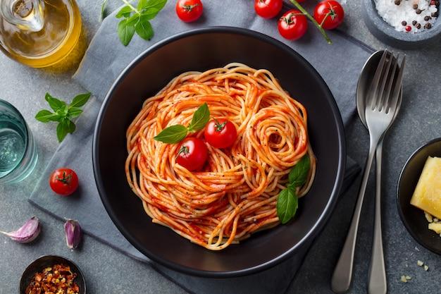 Macarrão, espaguete com molho de tomate em uma tigela preta. vista do topo. Foto Premium