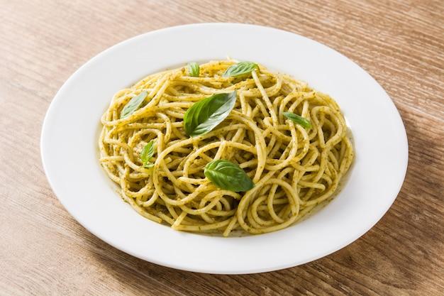 Macarrão espaguete com molho pesto na mesa de madeira Foto Premium