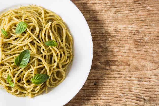 Macarrão espaguete com molho pesto no espaço da cópia de mesa de madeira Foto Premium