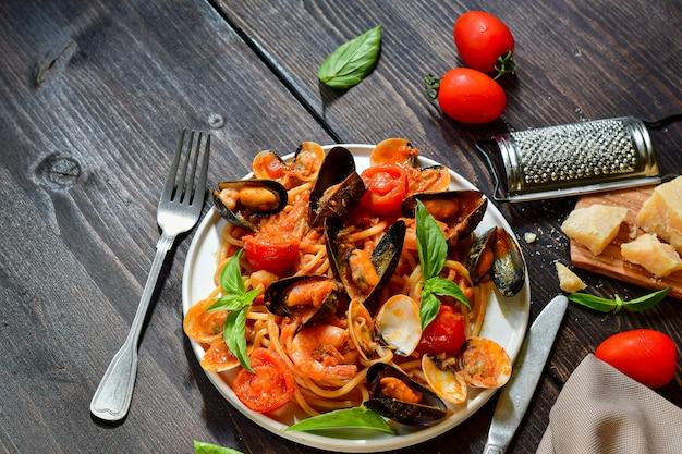 Macarrão espaguete de frutos do mar com amêijoas e camarões com mexilhões e tomates em um prato branco com uma mesa de madeira. receita da culinária italiana. vista do topo Foto Premium