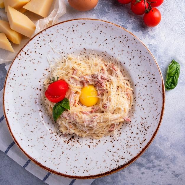 Macarrão espaguete italiano clássico com bacon, ovo, queijo parmesão e molho de natas. vista do topo. Foto Premium