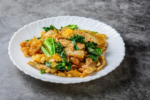 Macarrão fresco salteado da arroz-farinha com carne de porco, o ovo e a couve cortados. macarrão rápido salteado. Foto Premium