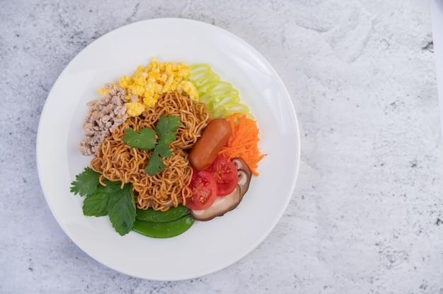 Macarrão frito com carne de porco picada, edamame, tomate e cogumelos em um prato branco. Foto gratuita