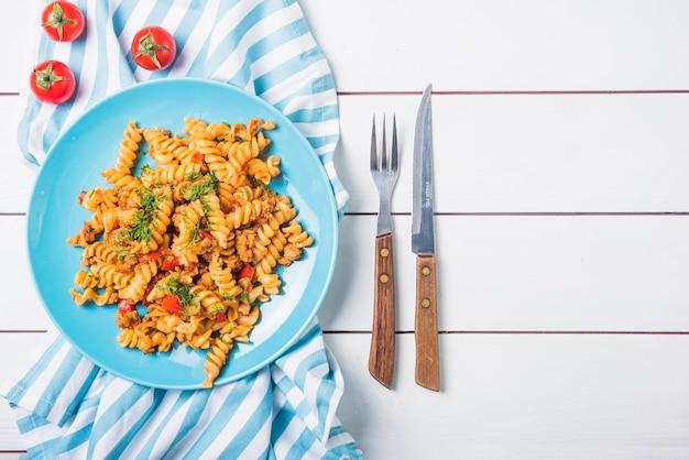 Macarrão fusilli com tomate e talheres na mesa de madeira branca Foto gratuita