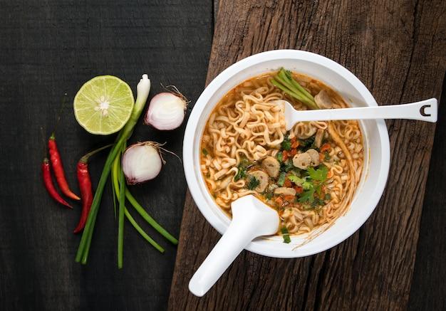 Macarrão instantâneo em tigela de plástico e pratos de legumes na madeira Foto Premium