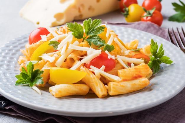 Macarrão, macarrão com molho de tomate e queijo em um prato sobre uma mesa de madeira. Foto Premium