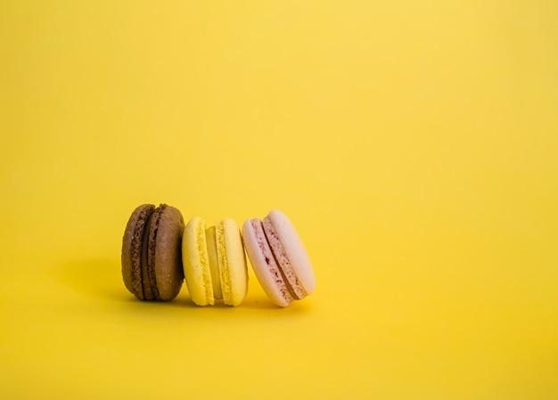 Macarrão marrom, amarelo e rosa são lateralmente em uma fileira. conjunto de três macarons em um espaço amarelo com espaço de cópia. Foto Premium
