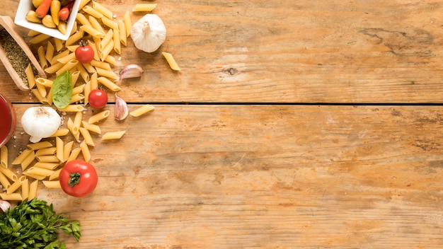 Macarrão penne com ingredientes de legumes na mesa de madeira velha Foto gratuita