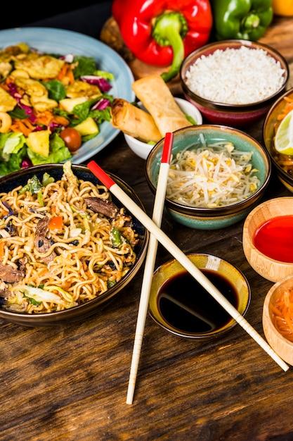 Macarrão tailandês; salada; rolinho primavera; arroz; brotos de feijão; molhos com pauzinhos na mesa de madeira Foto gratuita