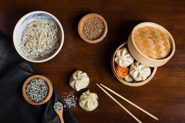 Macarrão udon com sementes de gergelim; sementes de coentro com bolinhos e pauzinhos na mesa de madeira Foto gratuita