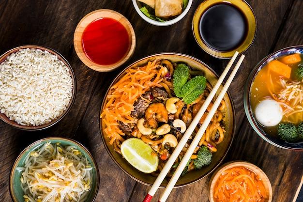 Macarrão udon de culinária tailandesa com molho de soja; arroz; brotos de  feijão e sopa na mesa | Foto Grátis