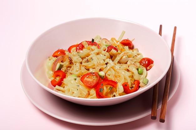 Macarrão vegano com ervilhas, pimentões, cebola e abobrinha Foto Premium