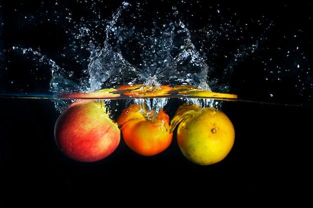 Maçãs e laranja espirrando em respingos de água azul claro Foto Premium