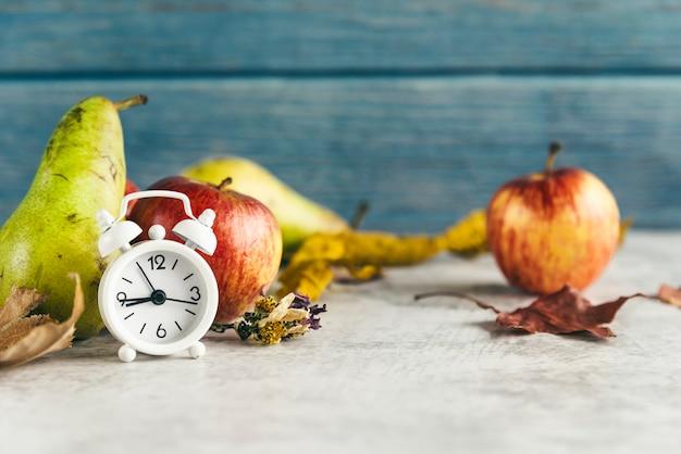 Maçãs e peras perto de despertador Foto gratuita