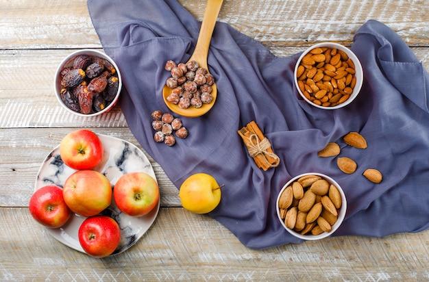 Maçãs em um prato com paus de canela, tâmaras, amêndoas descascadas e com casca em tigelas, nozes em colher de pau vista superior em madeira e têxteis Foto gratuita