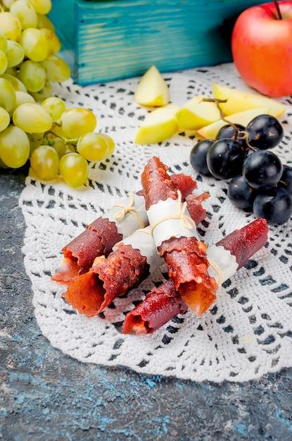 Maçãs frescas colhidas e uvas e frutas pastille em fundo escuro Foto Premium