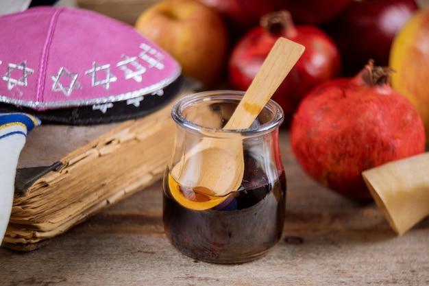 Maçãs, romã e mel para o livro da torá de rosh hashaná, kipá um yamolka talit Foto Premium