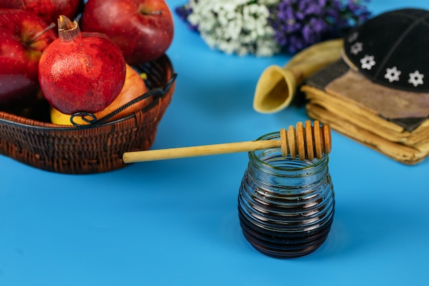 Maçãs, romã e mel para rosh hashaná livro da torá, kipá um yamolka Foto Premium