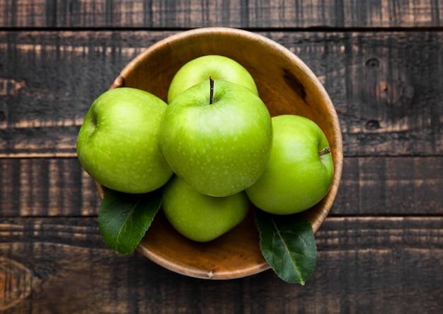 Maçãs saudáveis orgânicas verdes em tigela na placa de madeira Foto Premium