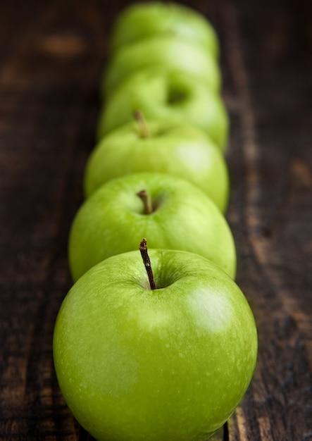 Maçãs saudáveis orgânicas verdes na placa de madeira Foto Premium