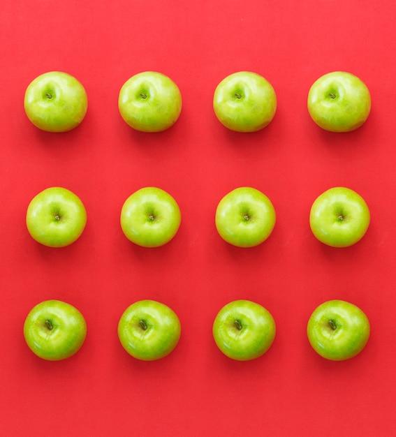 Maçãs verdes frescas em fundo de papel vermelho Foto Premium