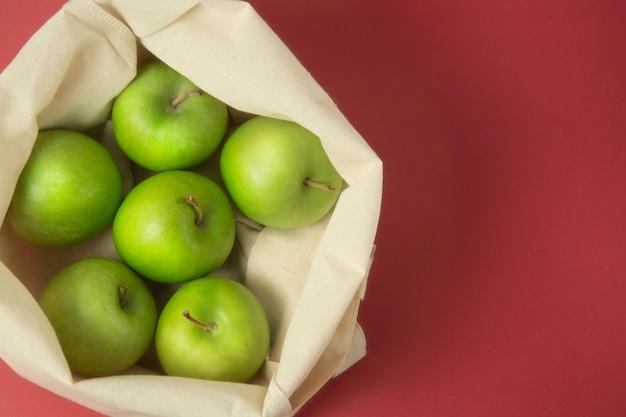 Maçãs verdes na sacola sobre fundo vermelho. zero conceito de desperdício. Foto Premium