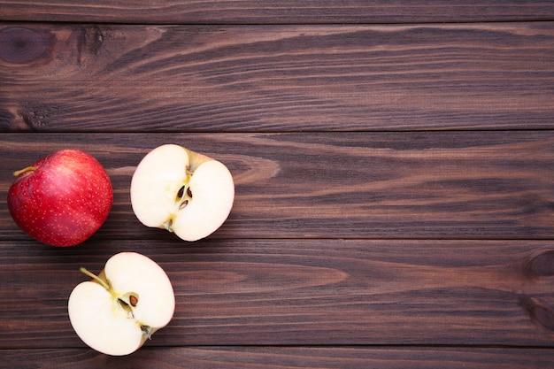 Maçãs vermelhas frescas em um fundo de madeira marrom Foto Premium