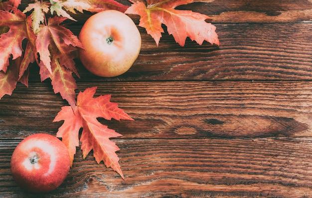 Maçãs vermelhas maduras e folhas de bordo coloridas no outono Foto Premium