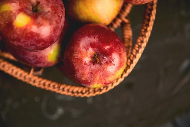Maçãs vermelhas orgânicas frescas em uma cesta no preto Foto Premium