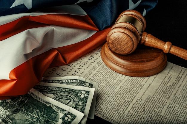 Macete de juiz de madeira com notas de dólares na bandeira dos eua com declaração de independência Foto Premium