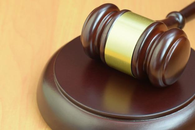 Macete de justiça na mesa de madeira em um tribunal durante um julgamento judicial Foto Premium