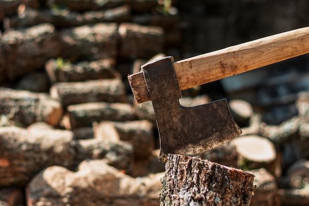 Machado enferrujado em um tronco de árvore Foto gratuita