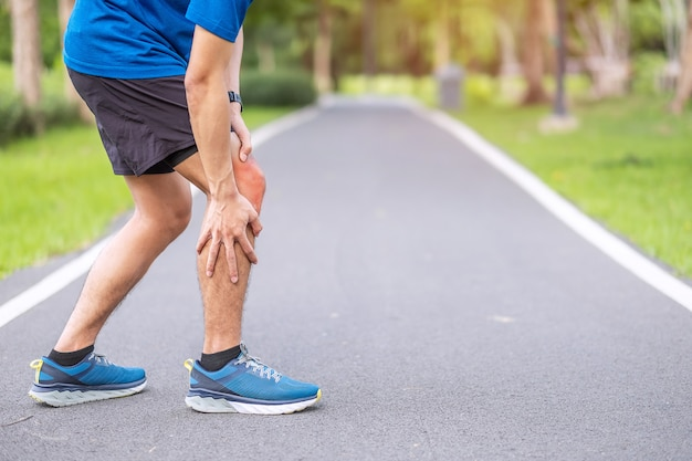 Macho adulto jovem com dores musculares durante a execução. o corredor tem dor no joelho devido à síndrome do joelho nos corredores ou da dor femoropatelar, osteoartrite e tendinite patelar. lesões esportivas e conceito médico Foto Premium