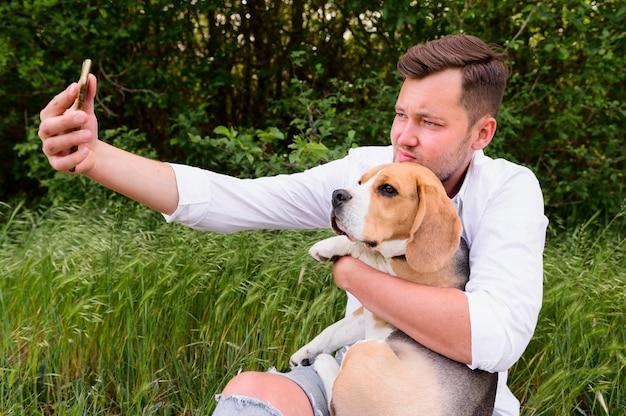 Macho adulto tomando uma selfie com cachorro fofo Foto gratuita