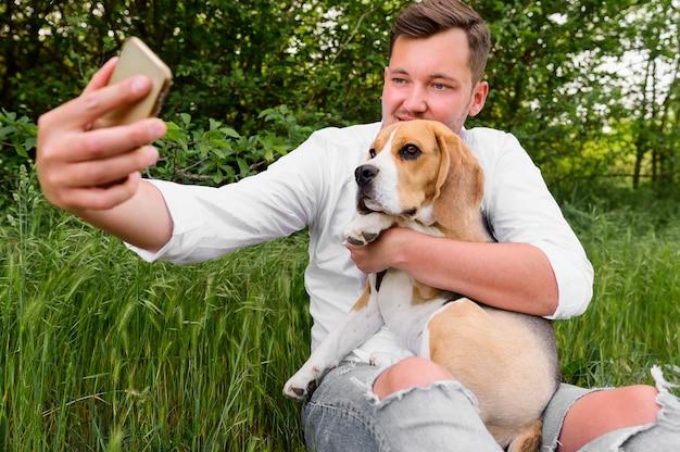 Macho adulto tomando uma selfie com seu cachorro Foto gratuita