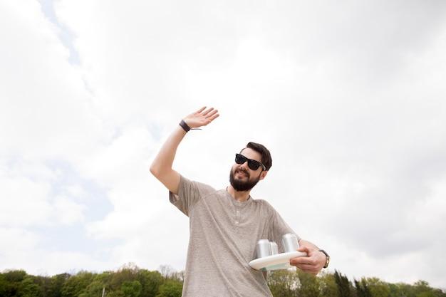 Macho alegre com bebidas acenando a mão Foto gratuita