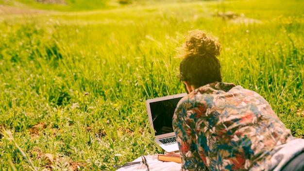 Macho assistindo no laptop na natureza Foto gratuita