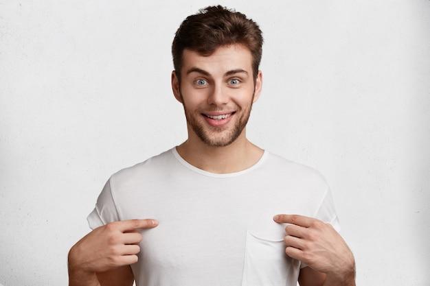 Macho barbudo positivo com barba por fazer, olhos azuis e expressão satisfeita, indica um espaço de cópia em branco na camiseta, isolado sobre o fundo branco. pessoas, bons sentimentos e conceito de propaganda Foto gratuita