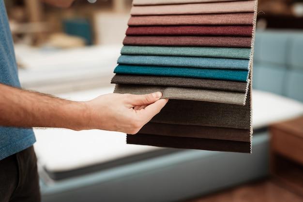 Macho cliente segurando amostras de têxteis multicoloridas Foto Premium