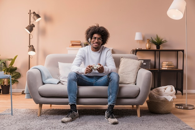 Macho com fones de ouvido jogando jogos Foto gratuita