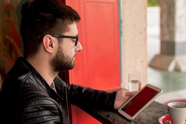 Macho com óculos de sol usando tablet Foto gratuita
